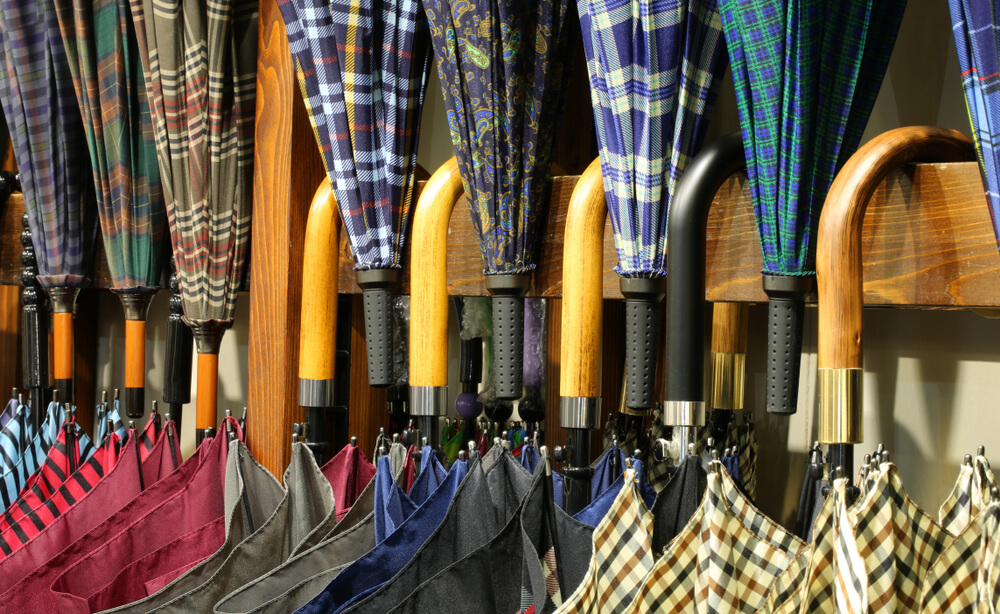 many umbrellas with wooden handles for sale in the shop specializing in fashion accessories