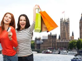 shopping, sale, tourism and people concept - two smiling teenage girls with shopping bags and credit card over london city